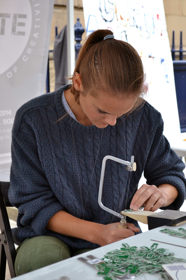 A young woman uses a piercing saw to cut into sheet metal.