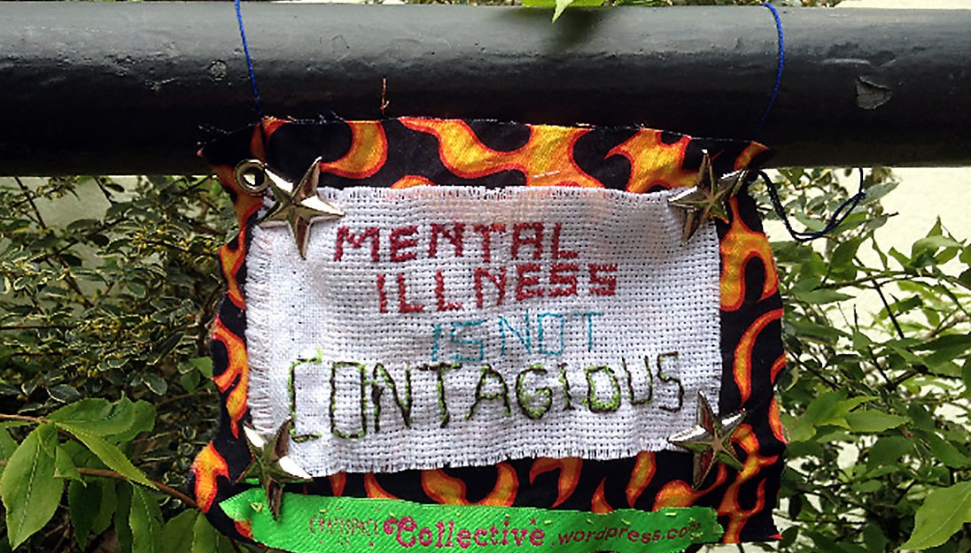 Sign made out of different fabrics with a stitched message about mental health and metal stars.