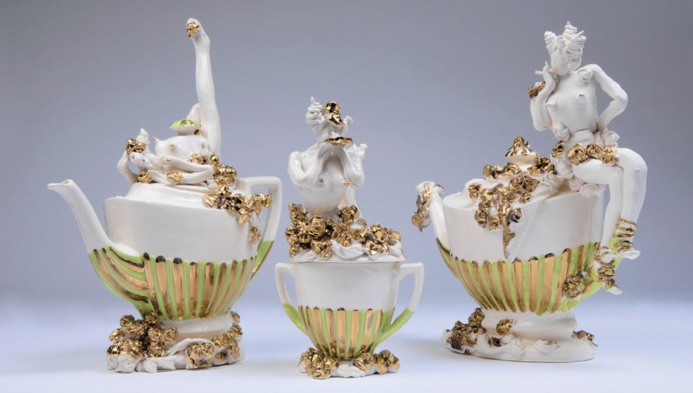 Three intricate and extravagent ceramic pots - two teapots and one lidded pot with gold roses and ladies.