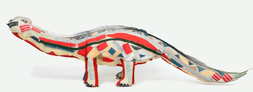 A 3D dinosaur made from textiles in a patchwork formation.