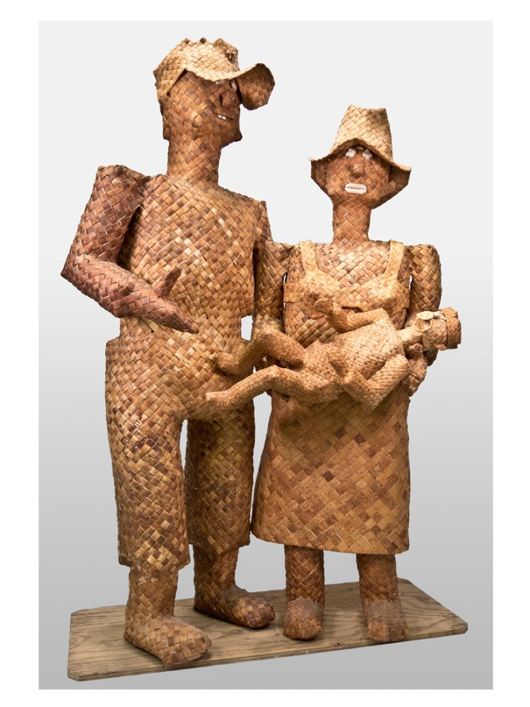 Three figurines, two adults holding a baby, woven from strips of wood.