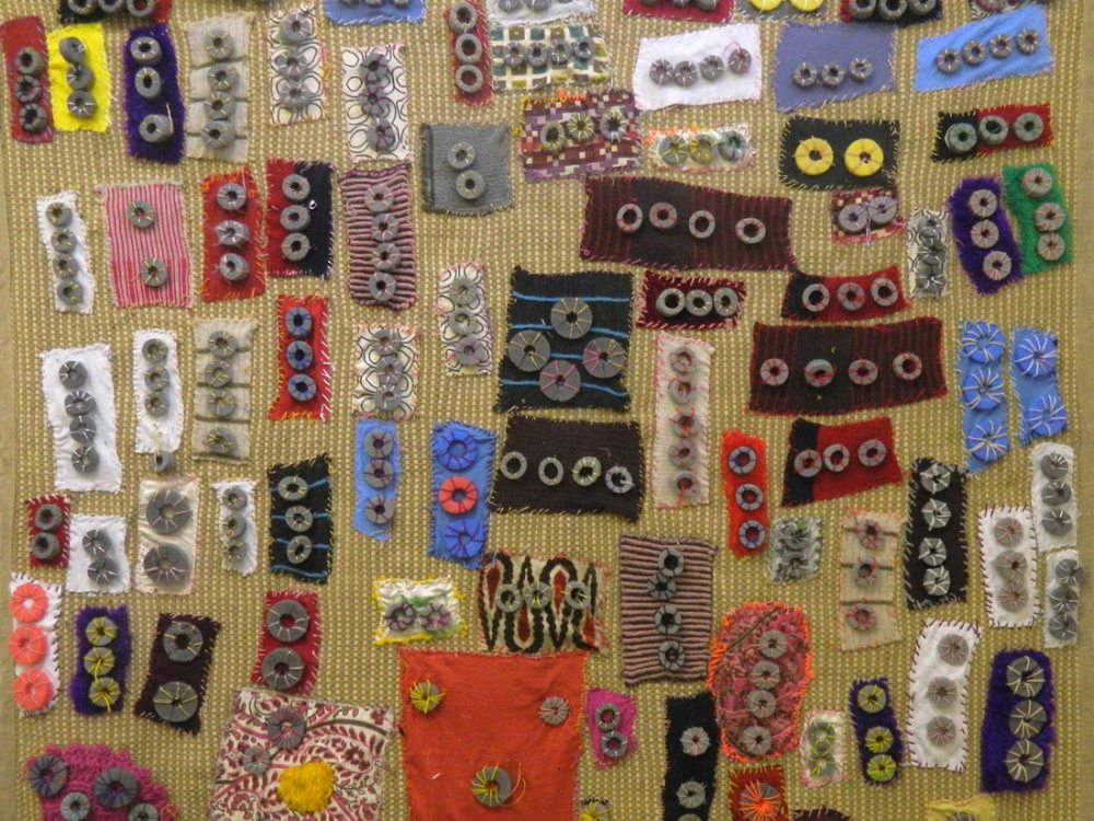 Close up of a rug with various patterned cloths stitched onto the surface with metal washers stitched on.