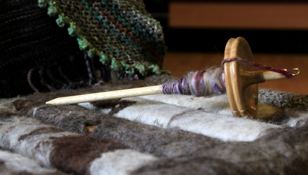 A drop spindle lies on a bench which has been covered with knitted pieces.
