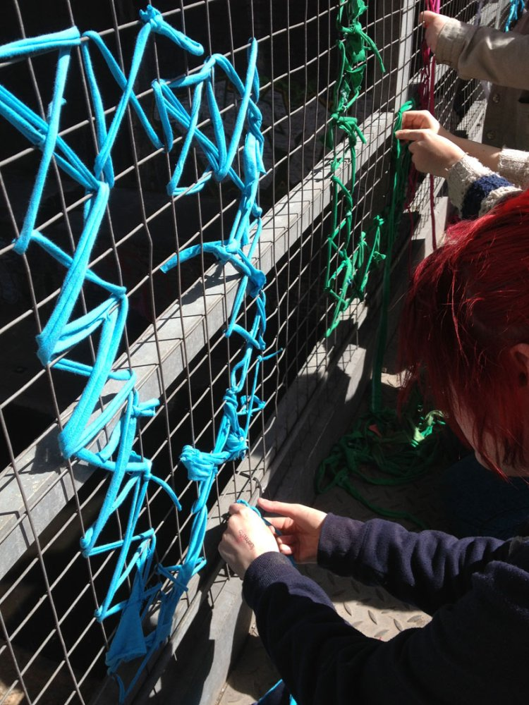 A woman weaves yarn through a metal gate to create the letter D.