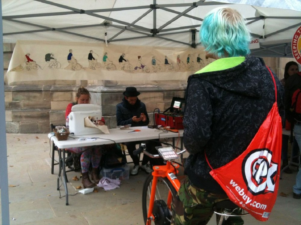 Outside, under a gazebo, a young man rides a stationary bike which is powering a sewing machine. A young woman sews and protraits of cyclists are hung around the space.