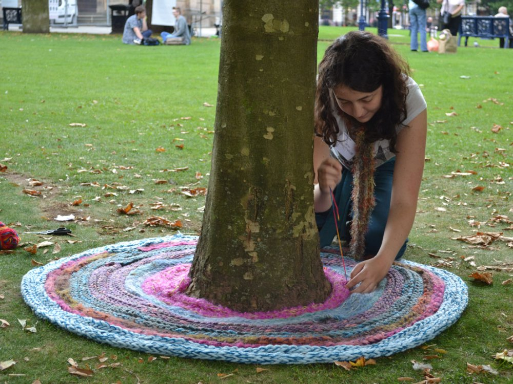 Sarah kneeling by a tree sewing together long strips of knitted wool to create a cirular shape around the bottom of the tree.