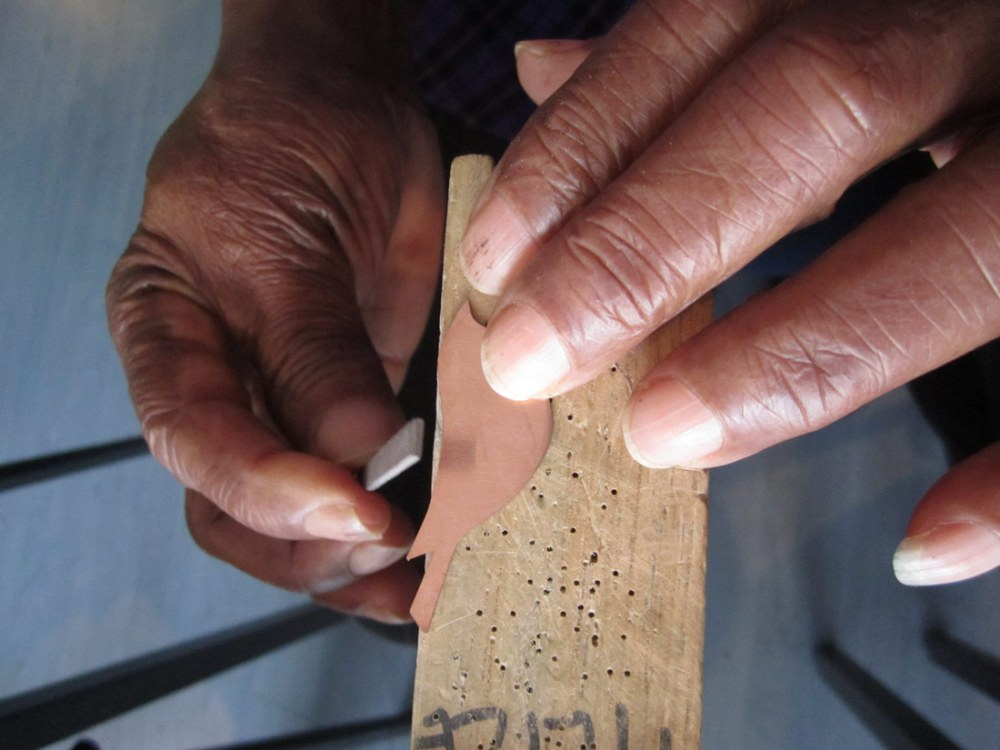 close up of Shelanu members hands filing one of the metal bird jewellery pieces