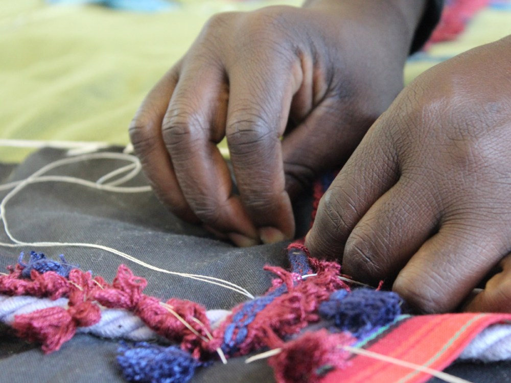 A close up of Andrew's hands carefully sewing different textures onto his textile works