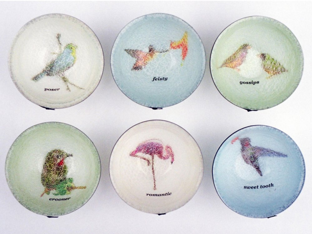 Six bowls with various images of birds inside of them with text underneath of a personality trait including 'romantic'.