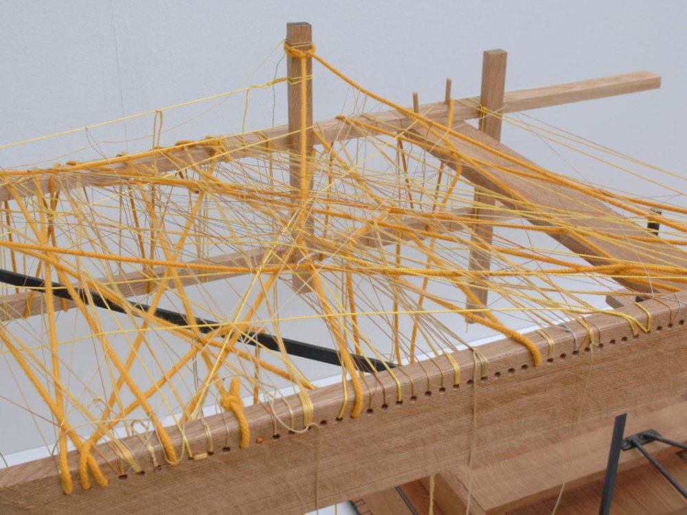 A close up of yellow thread woven between cuts of wood.