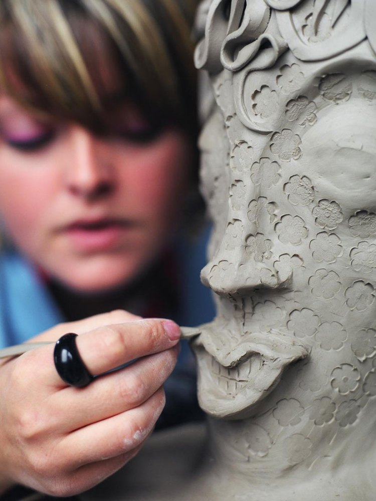 A close up of an artist carving lips into an intricate clay head.