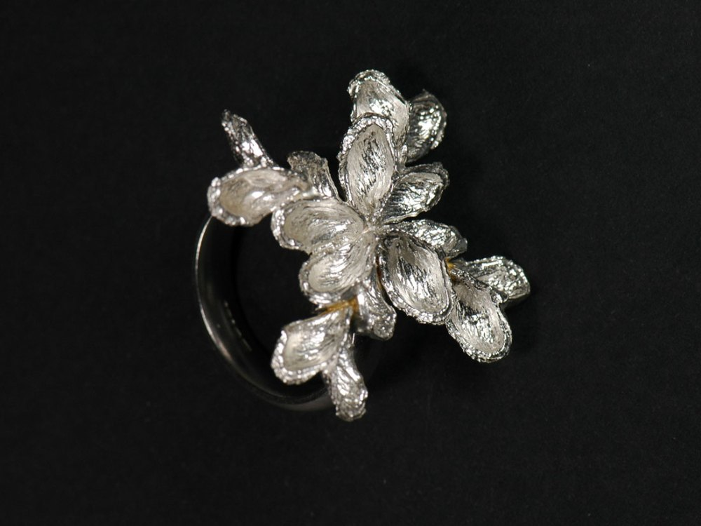 A metal ring with an intricate flower design.