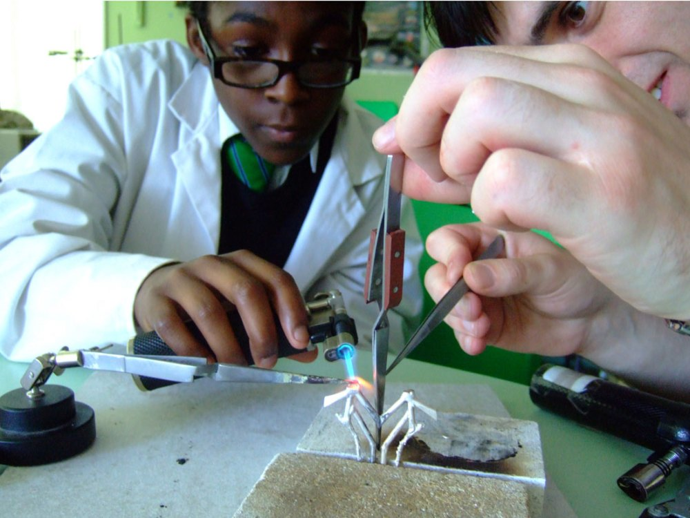 Two people work together to hold the metal together and solder.