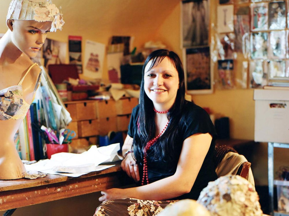 An artist sat in her studio smiling.