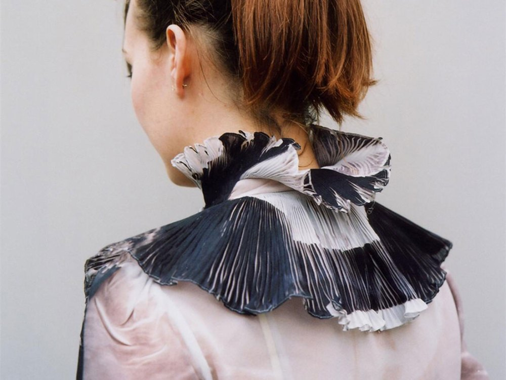 A lady wearing a delicate black and white adornment made from fabric.