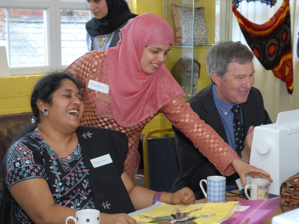 Two women laugh and smile whilst a man next to them uses a sewing machine.