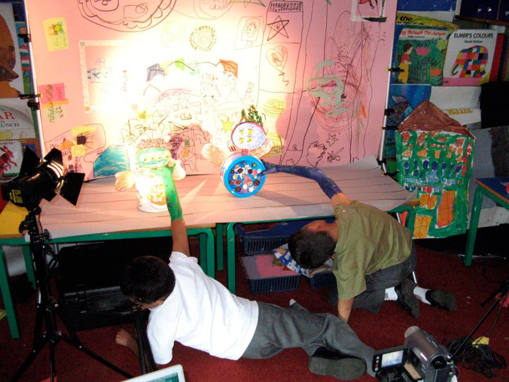 Two children use their figures made from found objects. They have drawn a backdrop setting and are using lighting.