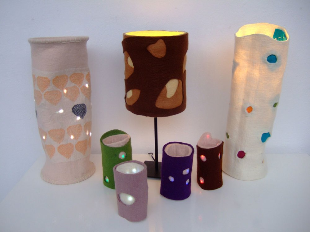 Seven light shades made out of felt of various colours with holes cut into them.