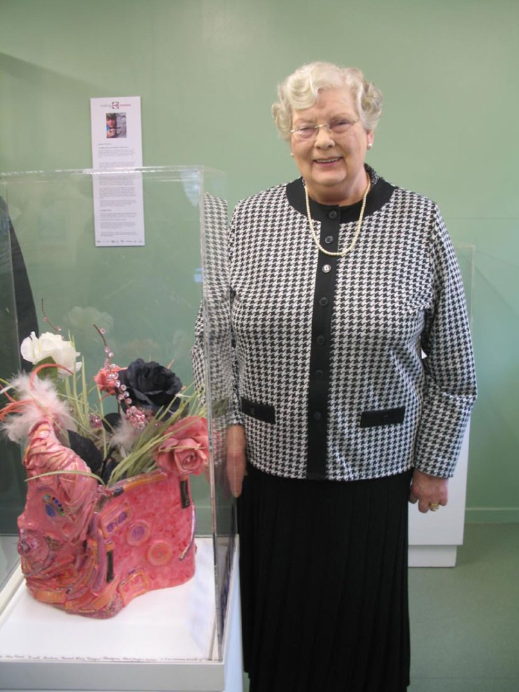 A lady stands next to an artwork inspired by her.