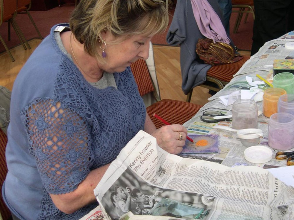 A woman sketches a design onto sheet metal with enamel powders placed on to the sheet metal.
