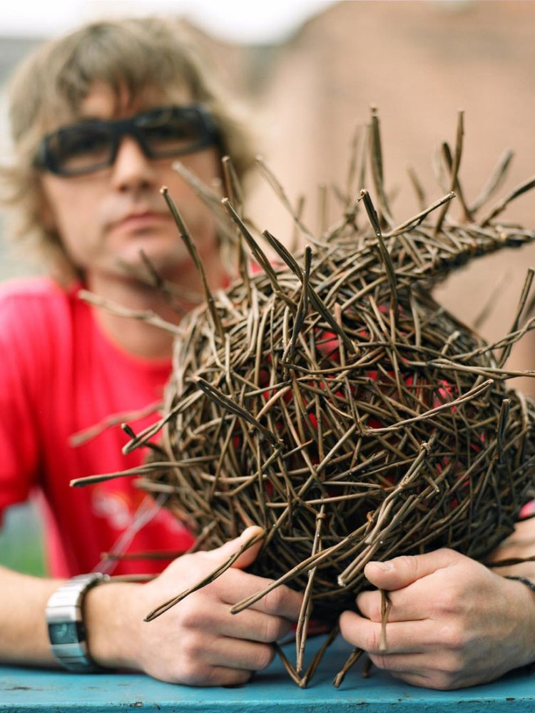 The artist holds a small sphere shaped intricate willow sculpture.