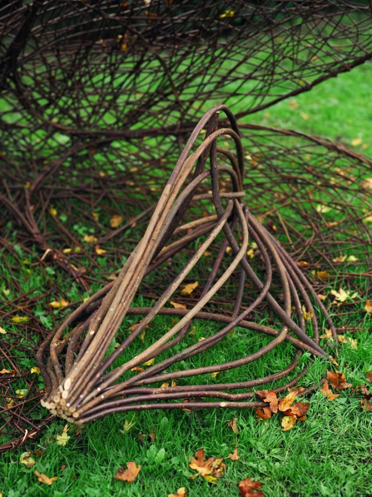 Various willow sculptures lie on the grass.