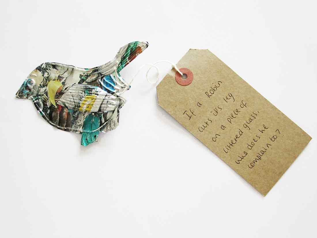 a bird shape cut from a thin printed metal attached to a luggage tag reading 'If a Robin cuts its leg on a piece of glass who does he complain to?'