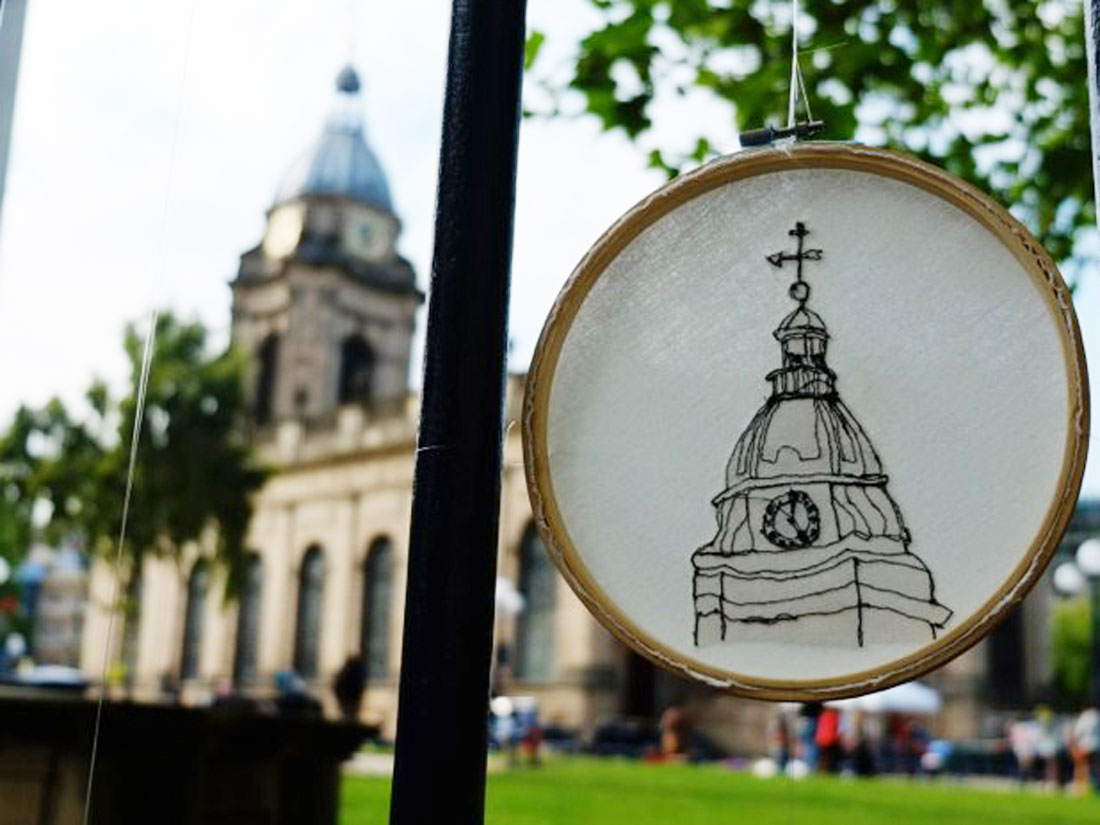 An emboidery ring hangs on the railings outside Birmingham Cathedral, the embroidery shows the clocktower of the same cathedral.