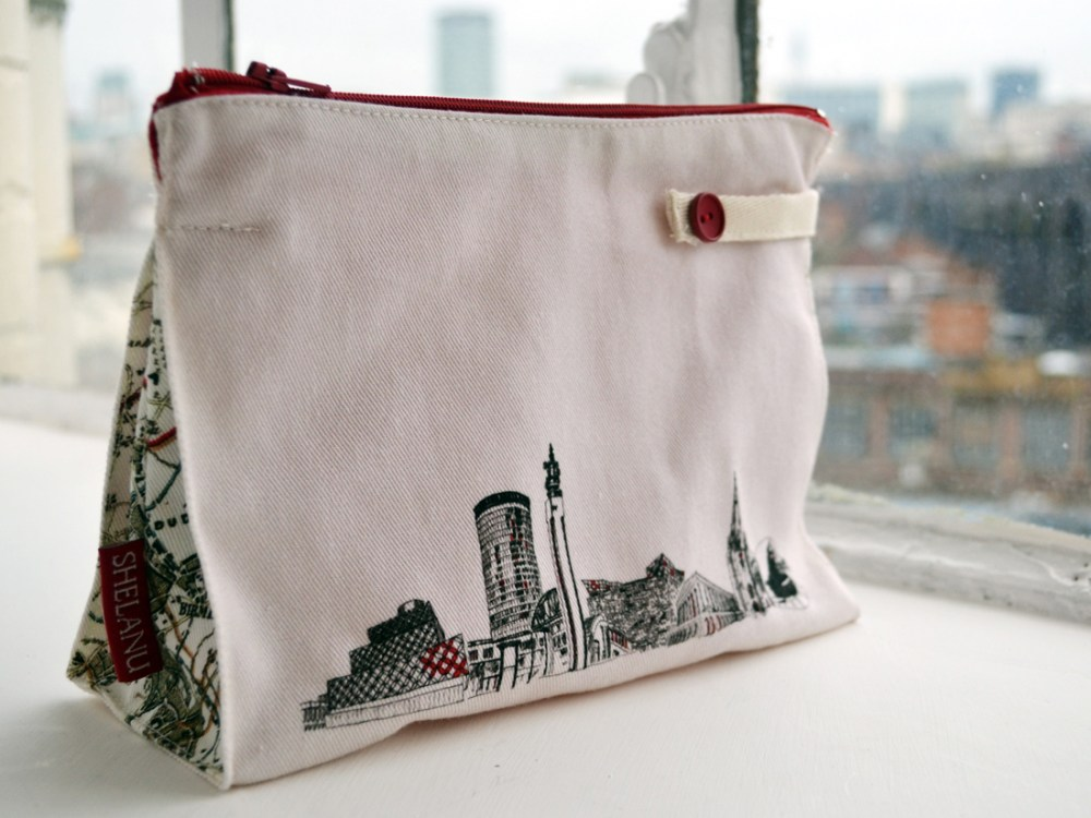 The wash bag sits on a windowsill. It is simple in design with a black and white line drawing of the skyline and red trimmings.