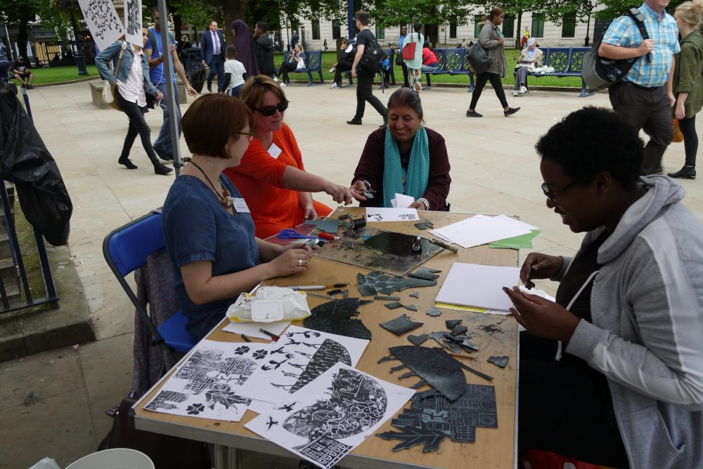 Four women of different ages are sat at a table in a public square making stencils. One woman is talking and pointing at something on the table and the other ones are laughing