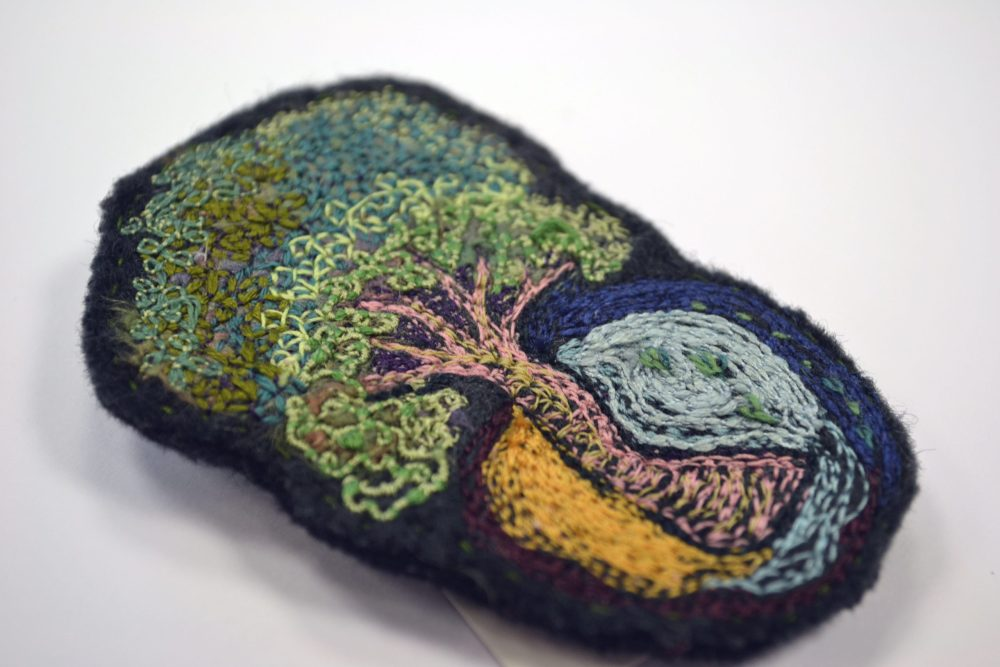 intricate embroidery patterns on felt of tree with surrounding patterns. colours include pale pink/green tree and background felt colour dark grey