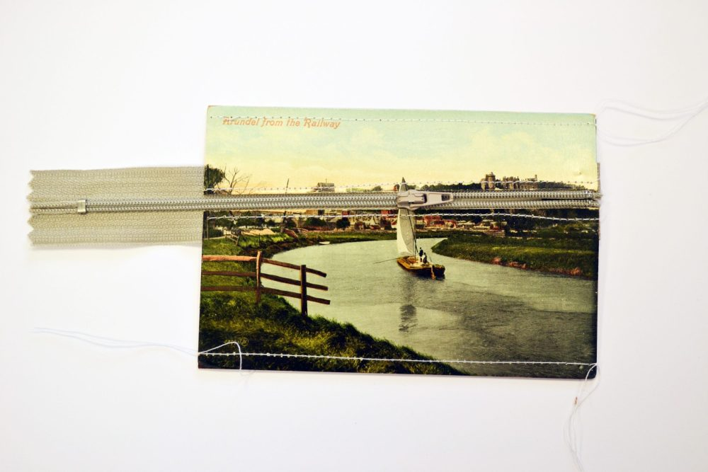 vintage postcard with image of Arundel featuring a grey zip going through the postcard revealing a second blank postcard underneath