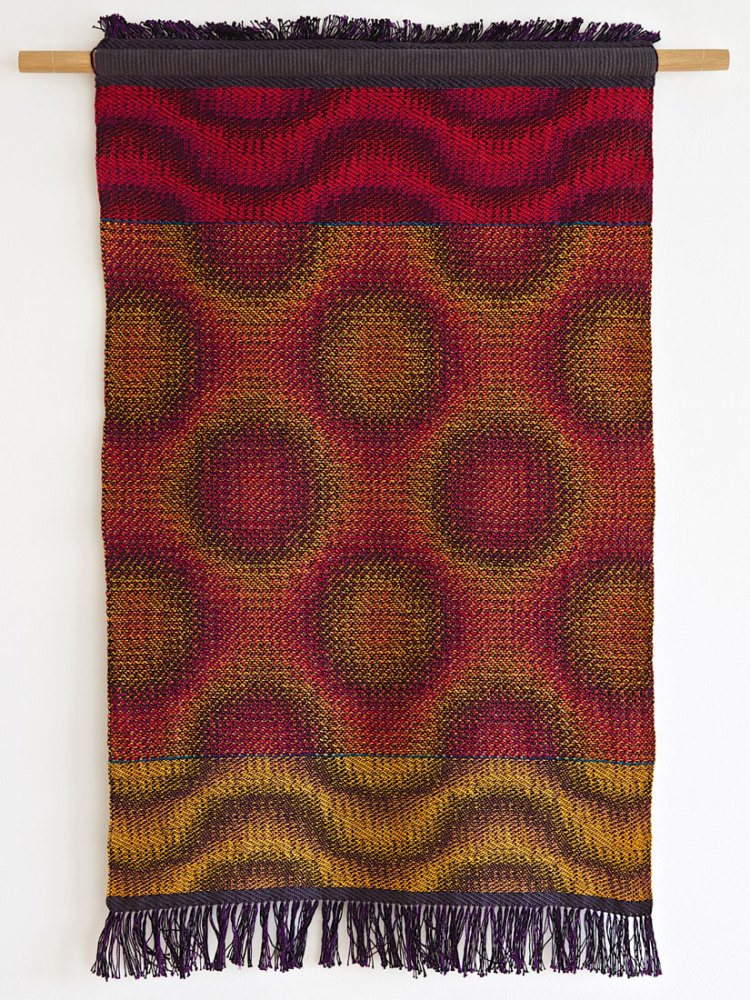 A woven piece of fabric of various colours hangs from a wall.