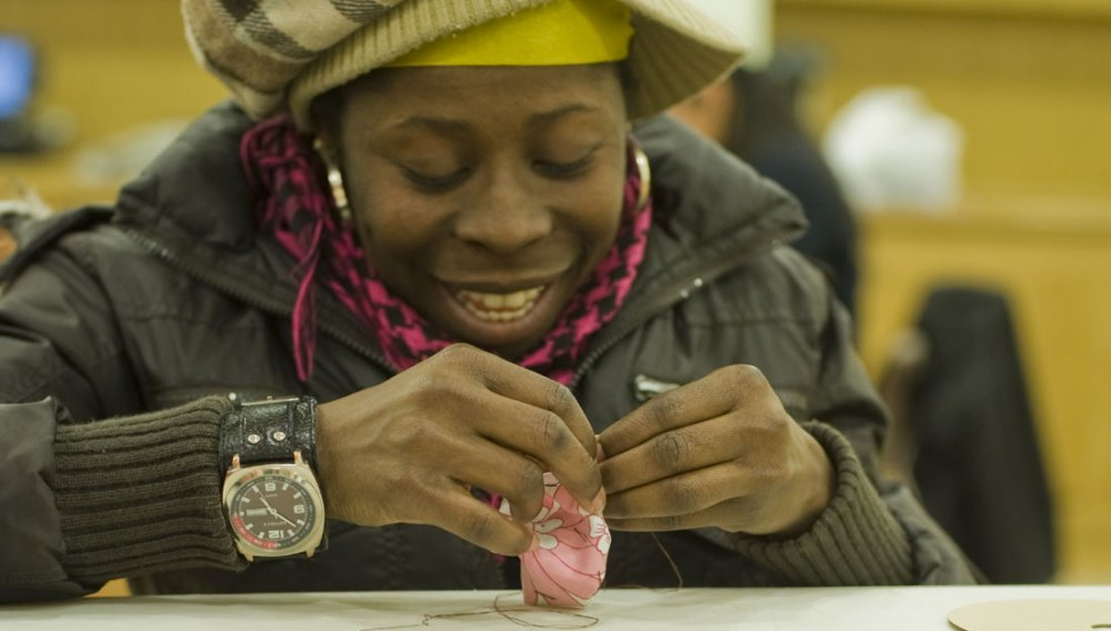 A lady smiles as she stitches into fabric using needle and thread.