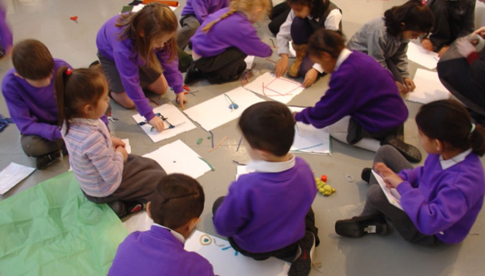 A group of school children sit on the floor using straws, pens and pencils to create drawings on their pieces of paper.