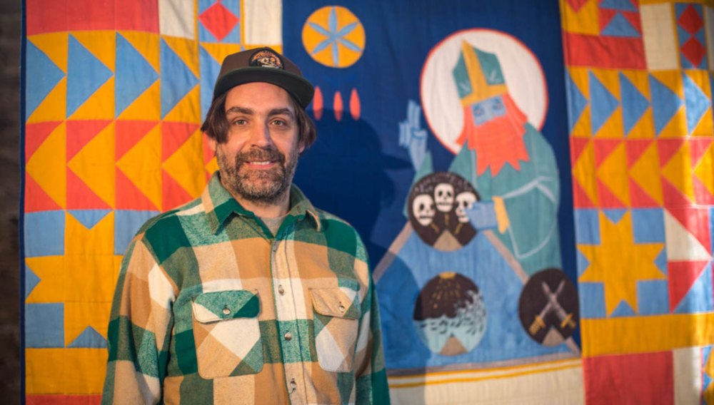 The artist stands infront of his brightly coloured tapestry.