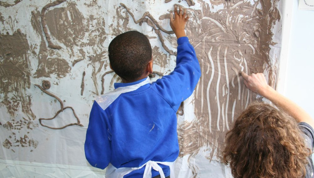A child uses clay and his hands to create line drawings on the wall.