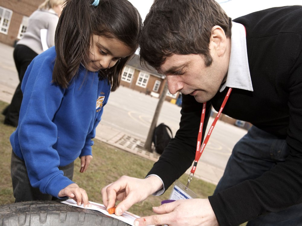 A man helps a young girl with creating texture on paper from a tyre.