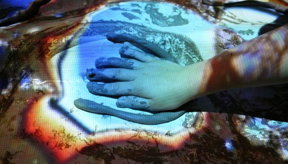 A tube of clay lies next to a hand covered in clay with images projected on to the hand.