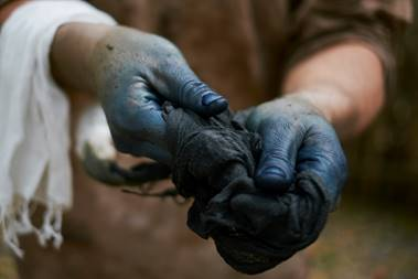Hands hold a piece of cloth. The cloth and the hands are stained blue with dye.