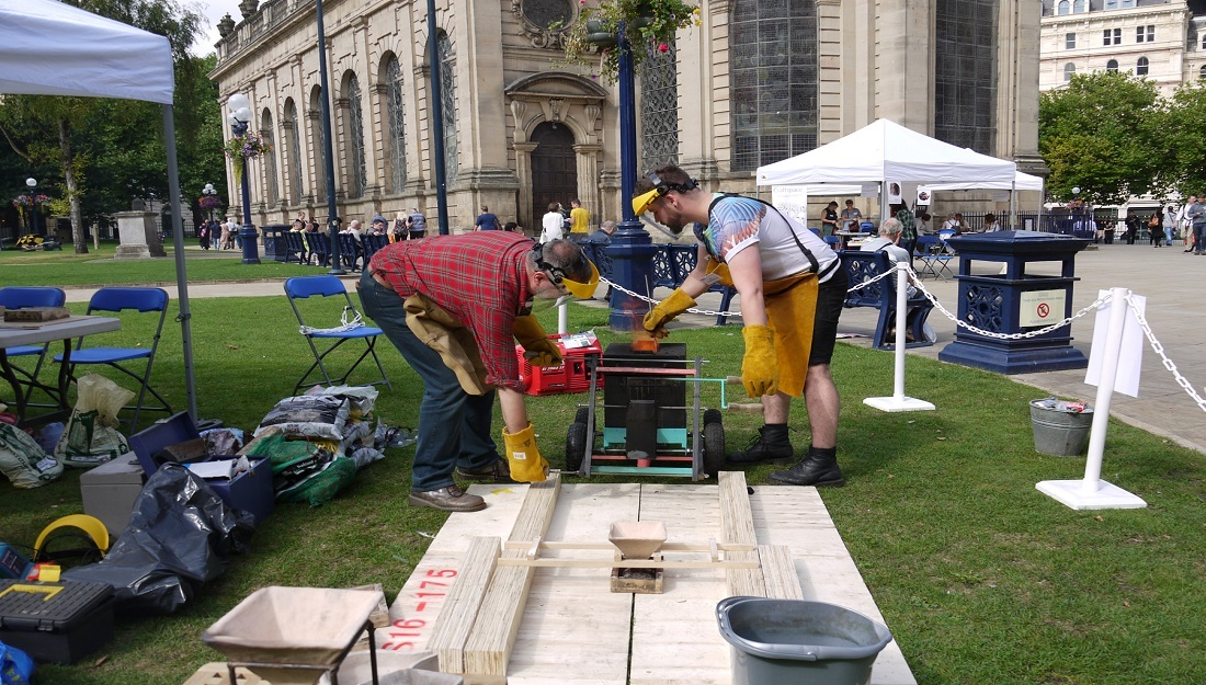 Two men pour molten metal into a mould, outside Birmingham Cathedral.