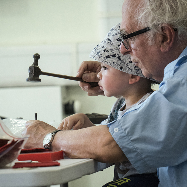 An older man works with a young boy hammering a metal punch.