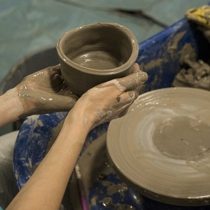 Hands holding a wet lcay pot, just off the potters wheel.