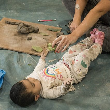 A baby, lying on a plastic sheet, is handed a lump of clay to play with.