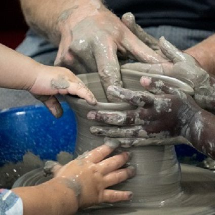 A mix of baby, toddler and adult hands all helping to throw a pot on the potter's wheel.