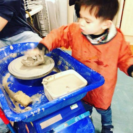A boy reaches to touch clay spinning on a potter's wheel.