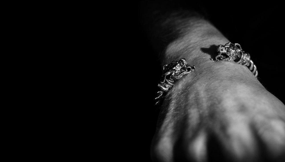 black and white photograph of silver dragon cuff