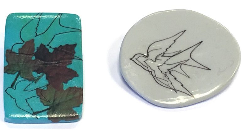 Two pendants - one white, one blue with bird and leaf backgrounds.