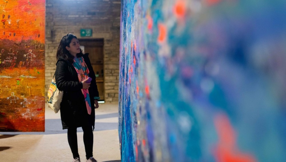 A delegate admires Alice Kettle's textile work.