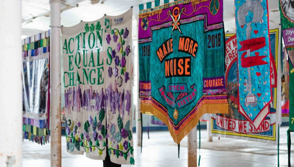 colourful banners hanging in space, reading 'Action Equals Change' and 'Make More Noise'